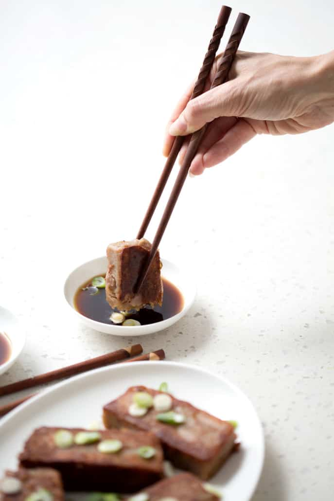 using chopsticks to dip the taro cake into the dip