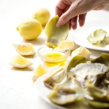 dipping artichoke leaf into aip lemon 'butter' artichoke dipping sauce
