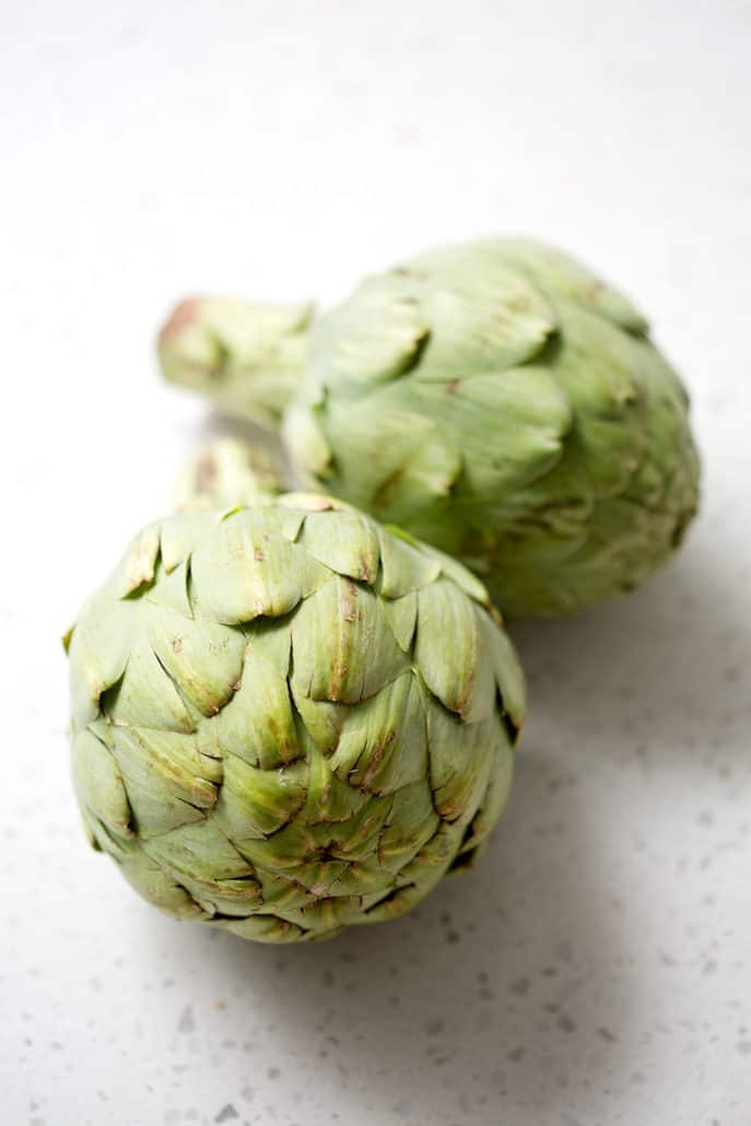 whole artichokes on white counter