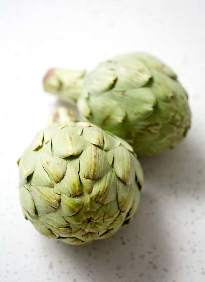 whole fresh artichokes on white background