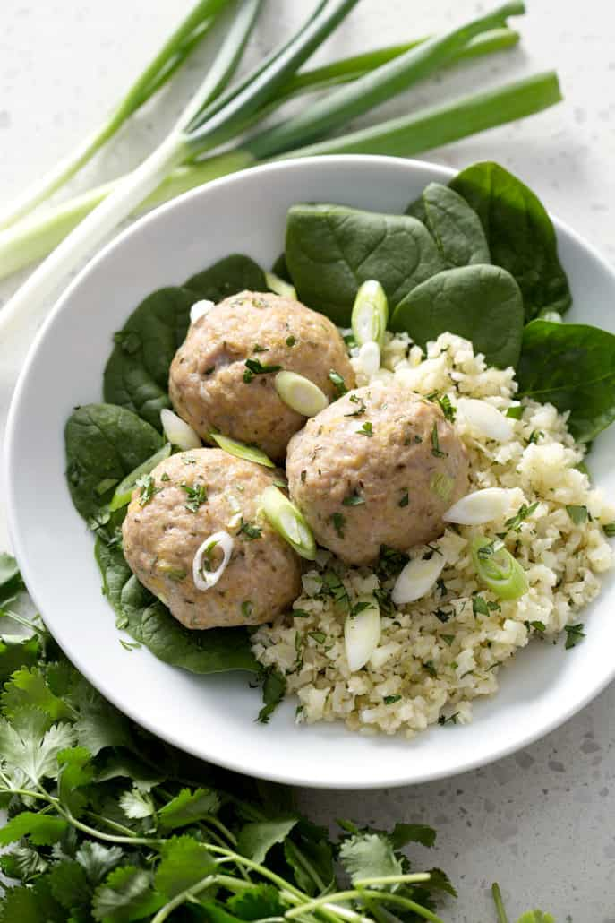meatballs on bed of cauliflower rice and spinach on white plate