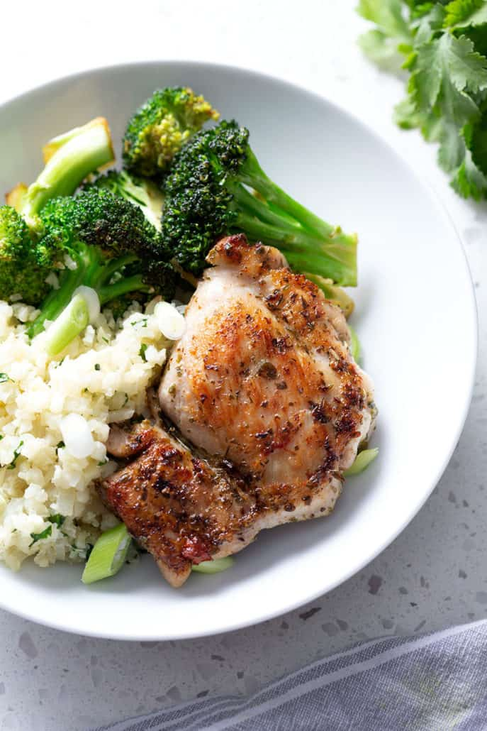Chicken thigh resting on rice and broccoli on white bowl