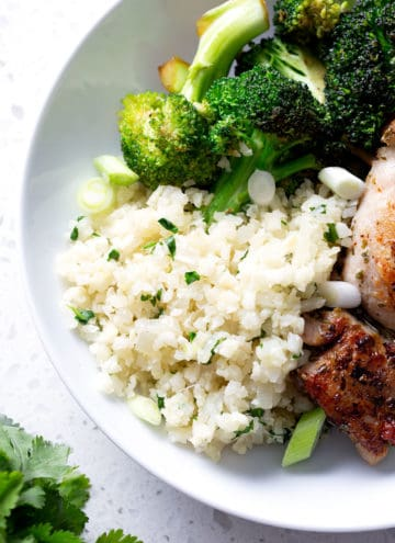 cauliflower rice with herbs in a white bowl with chicken and broccoli