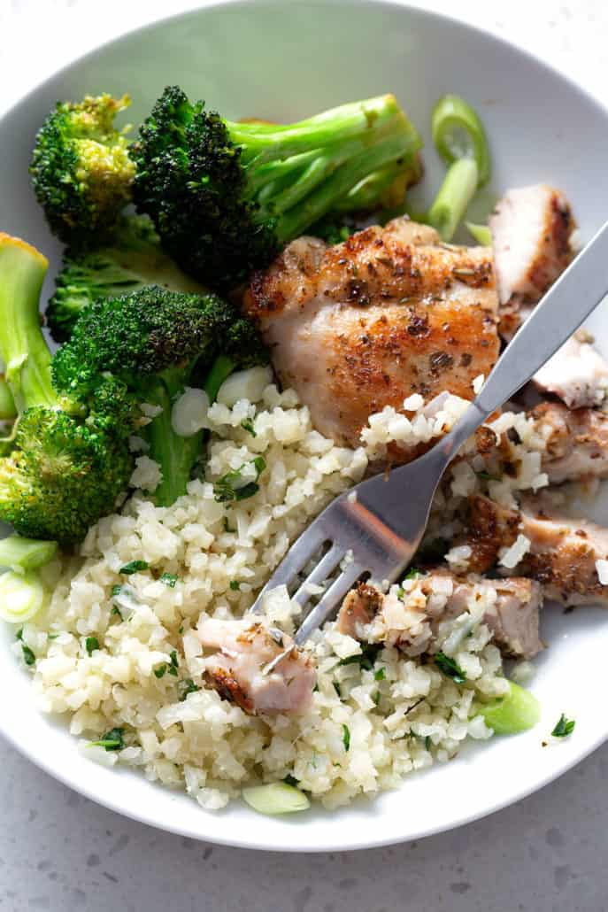 Bite of chicken on fork resting on rice and broccoli