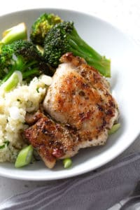 chicken on bed of rice with broccoli in white bowl