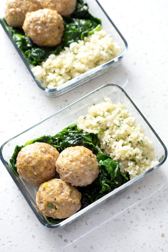 meatballs, spinach and rice in glass portable dishes on white counter