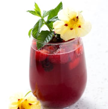 cocktail garnished with mint and flowers sitting on white background