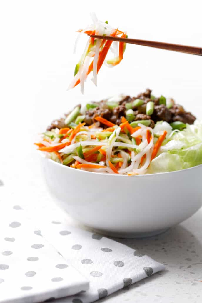 bowl of lettuce, shredded vegetables and ground beef with chopsticks
