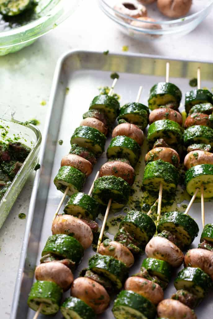 prepping skewers with veggies and meat on baking sheet