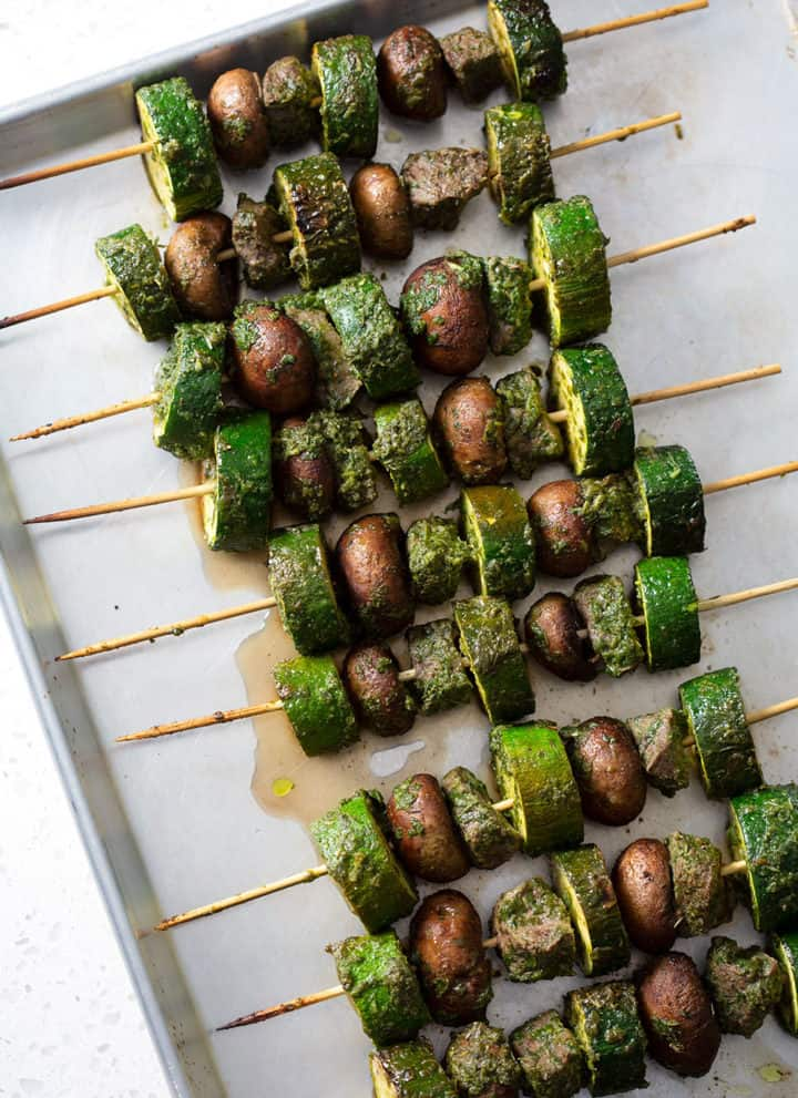 grilled meat skewers with vegetables on baking sheet