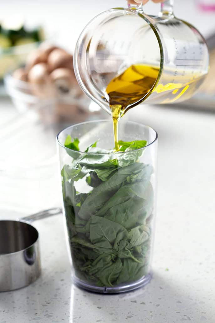 pouring olive oil into container stuffed with basil