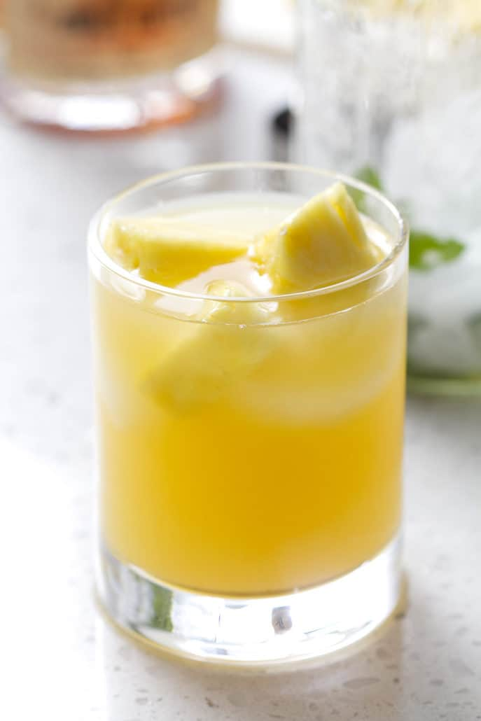 glass filled with juice and pineapple chucks