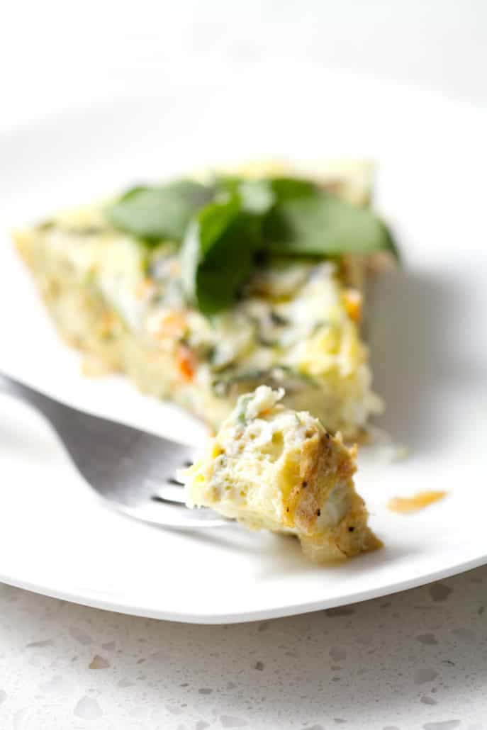 slice of frittata with bite on fork and garnished with basil