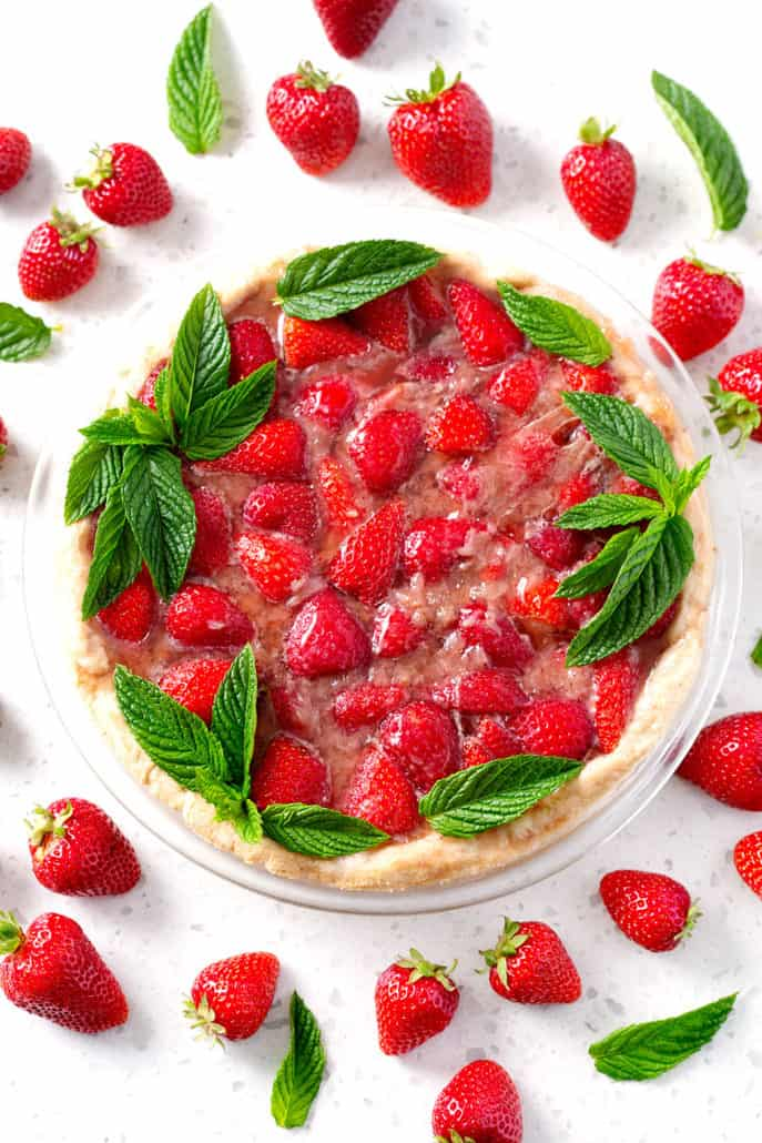 strawberry pie garnished with mint leaves and strawberries on white counter