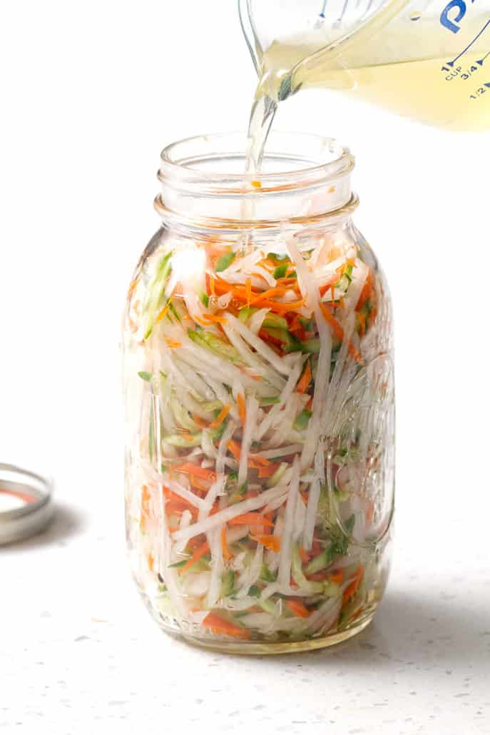 shredded vegetables in large mason jar on white counter