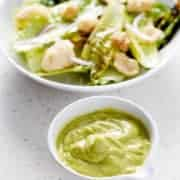 green salad dressing next to salad bowl