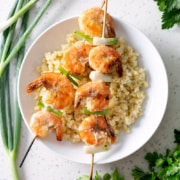 grilled garlic shrimp skewers on bed of rice on white plate