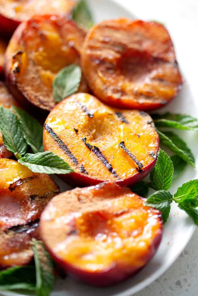 close up of grilled peaches on platter with min garnish
