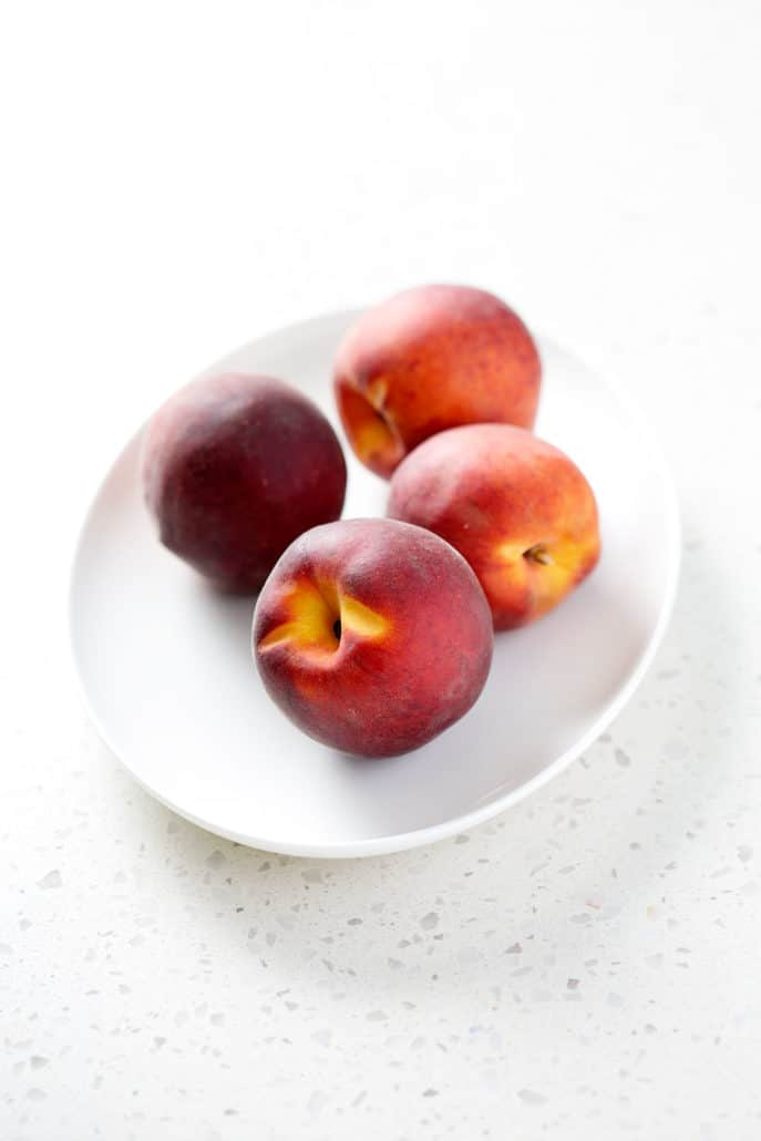fresh peaches on white platter on white counter