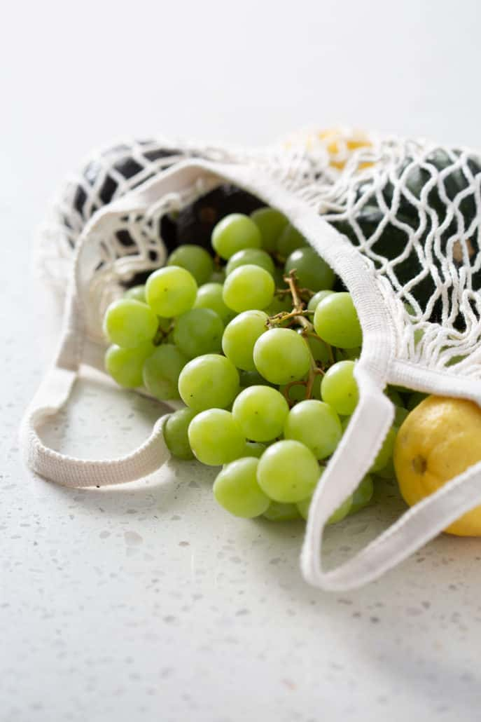 grocery bag with grapes and produce spilling out on white background