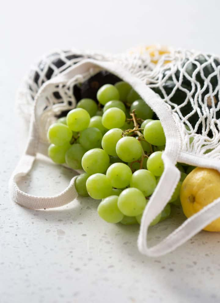 grapes and produce spilling out of a grocery bag on white counter