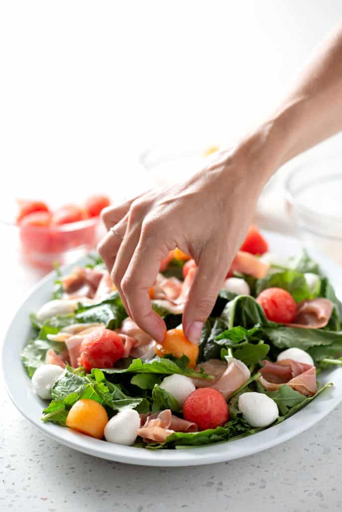 placing ingredients on platter of salad on white background