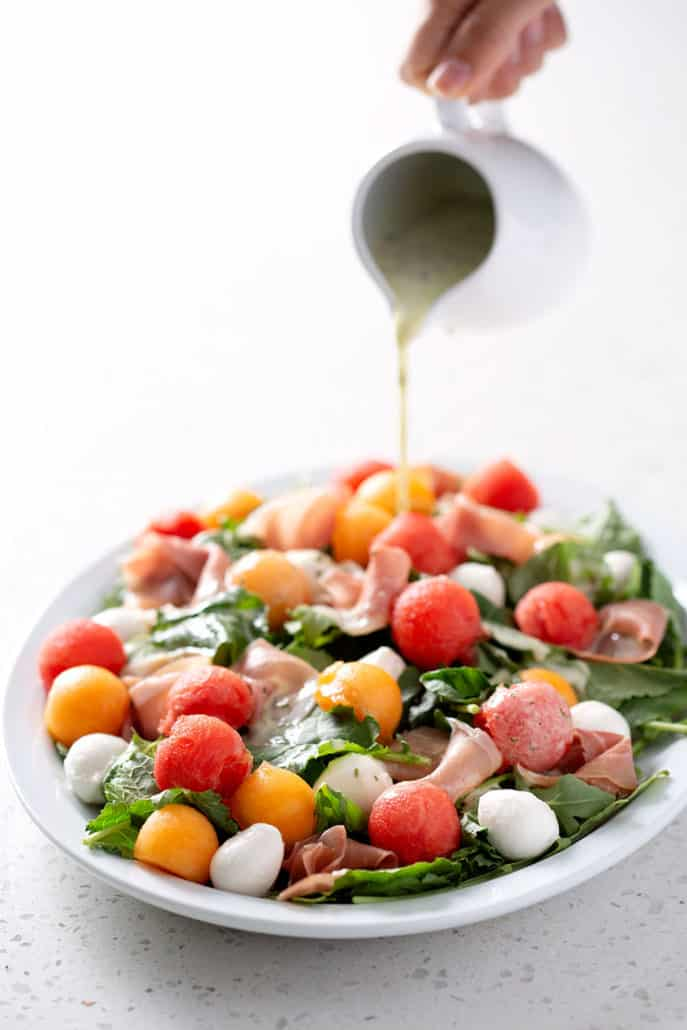pouring dressing over salad on platter on white background