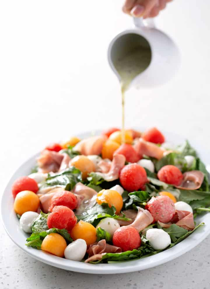 pouring dressing over platter of salad on white counter