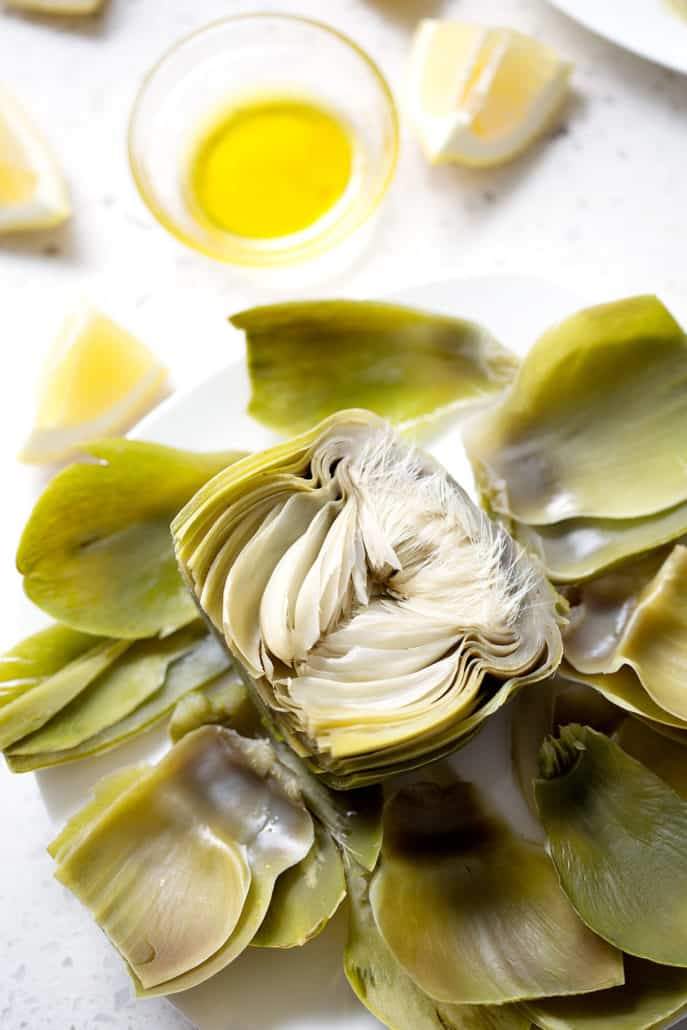 artichoke halved and cooked alongside a small bowl of artichoke dipping sauce