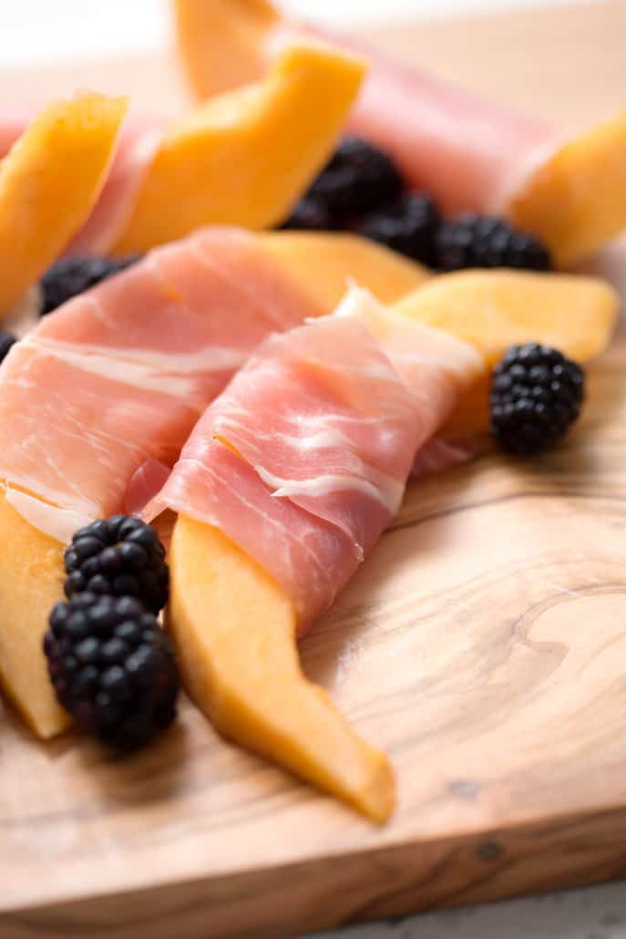 slices of cantaloupe wrapped in prosciutto on cutting board