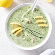 bowl of green soup with lemon and chive garnish from above