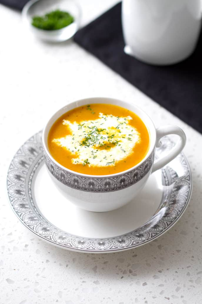 cup of soup with cream on whitecountertop