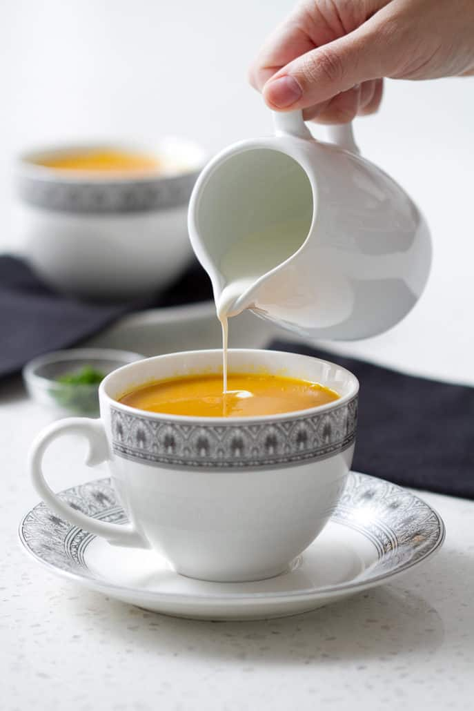 pouring cream into cup of soup