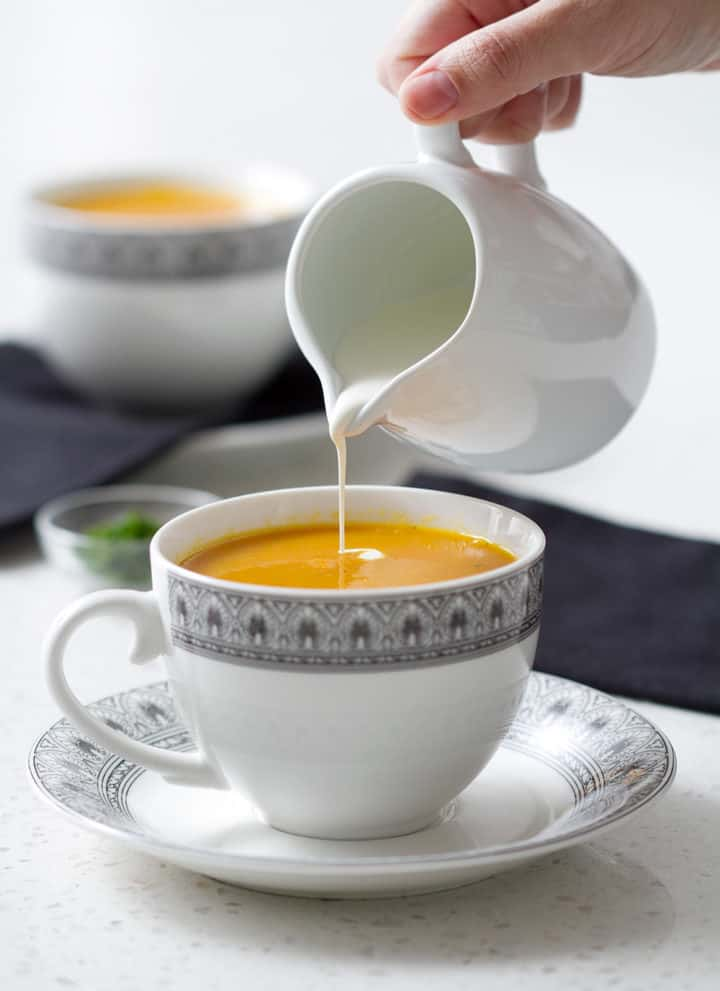pouring cream into carrot ginger soup