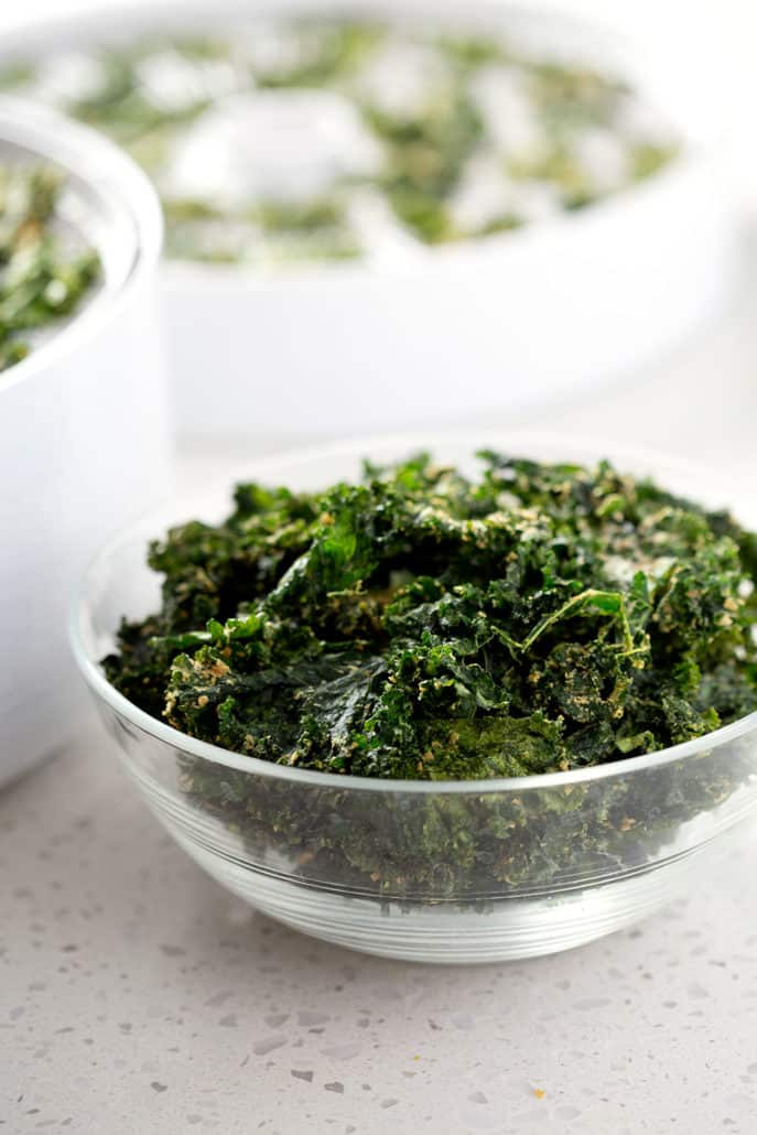 bowl of kale chips in front of dehydrator