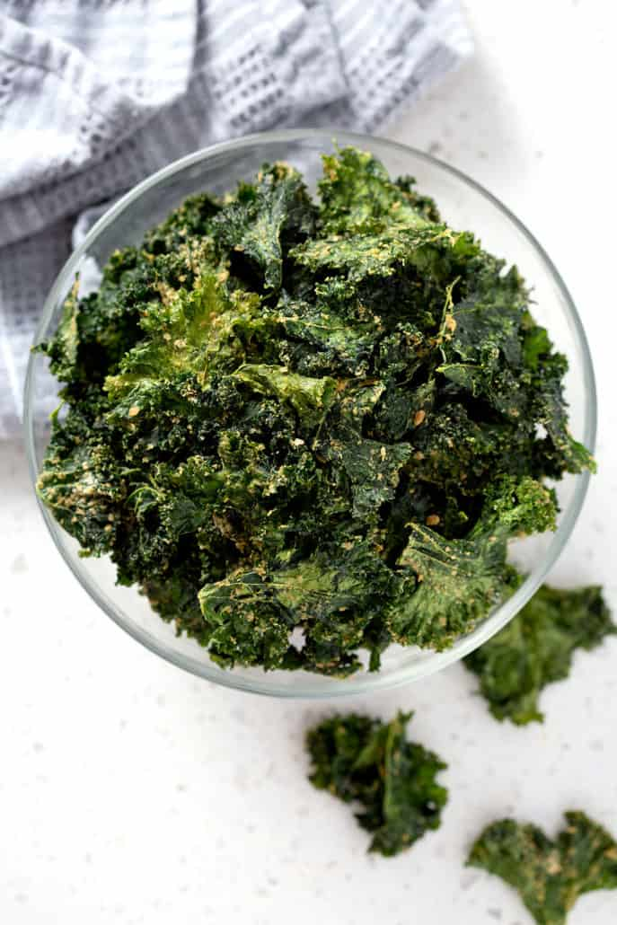 bowl of kale chips from above surrounded by towel and additional chips