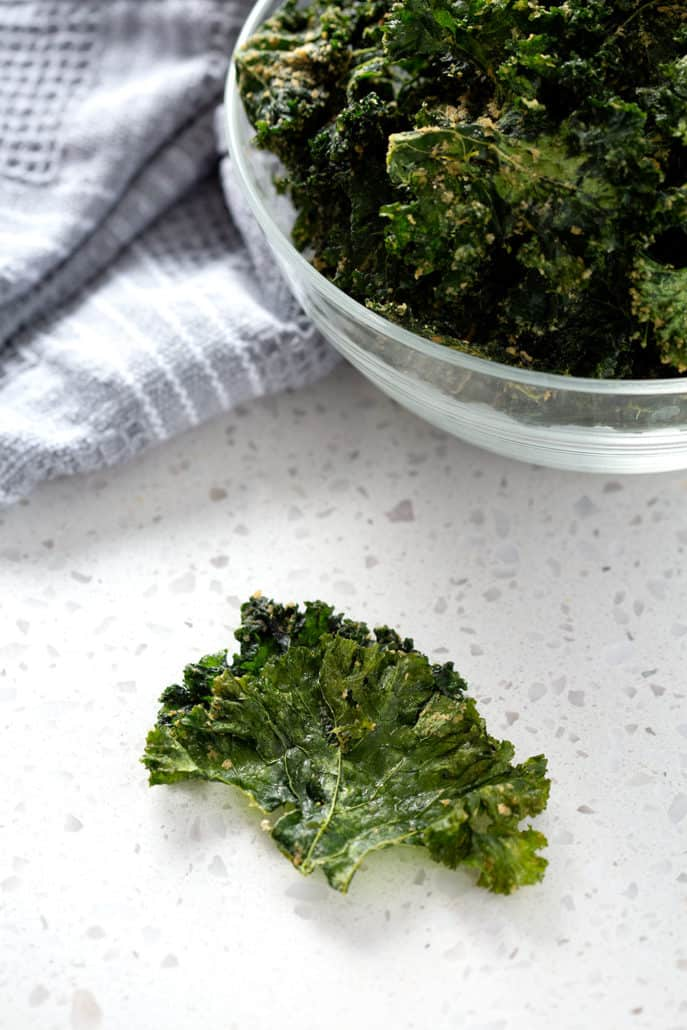 kale chip on counter in front of bowl of kale chips and towel