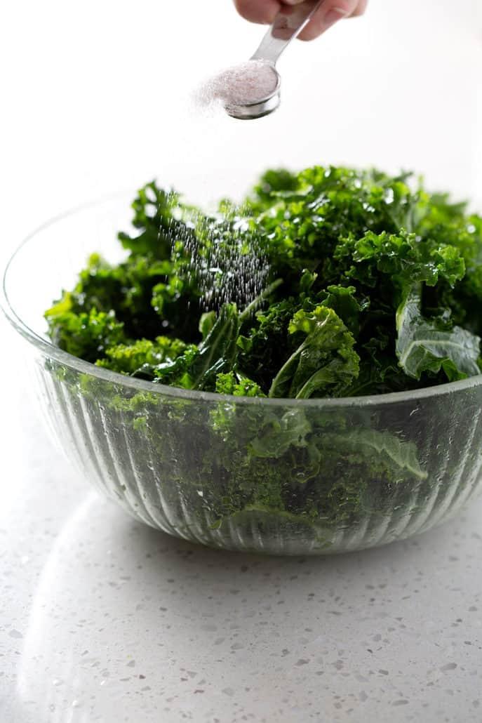action shot of sprinkling salt over bowl of kale