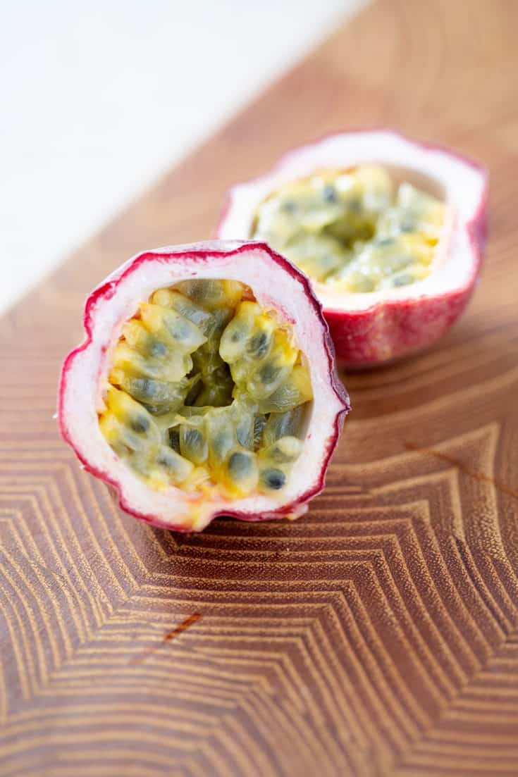 passion fruit cut in half exposing fruit on cutting board