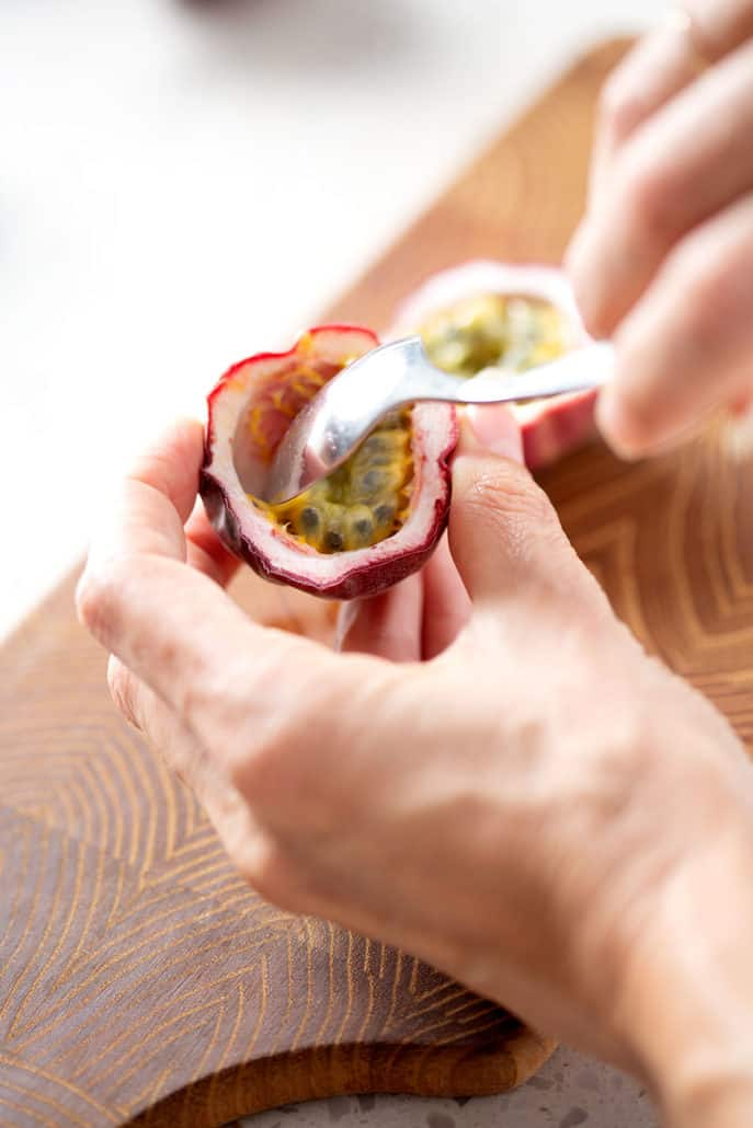 hands holding shell of passion fruit while scoping out insides with a spoon