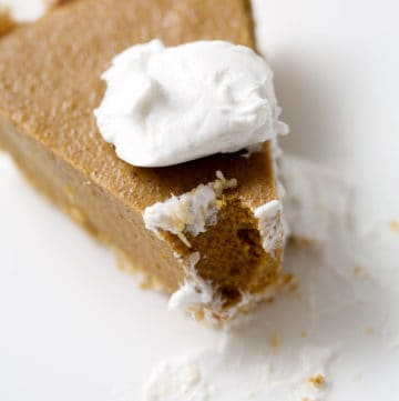 piece of pumpkin pie with dollop of cream close up