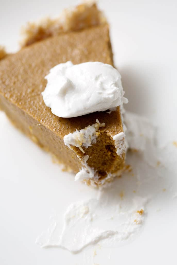 slice of pumpkin pie with dollop of cream on top