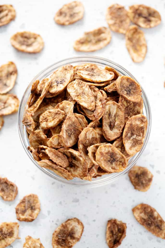 Bowl of dehydrated banana chips surrounded by banana chips from above