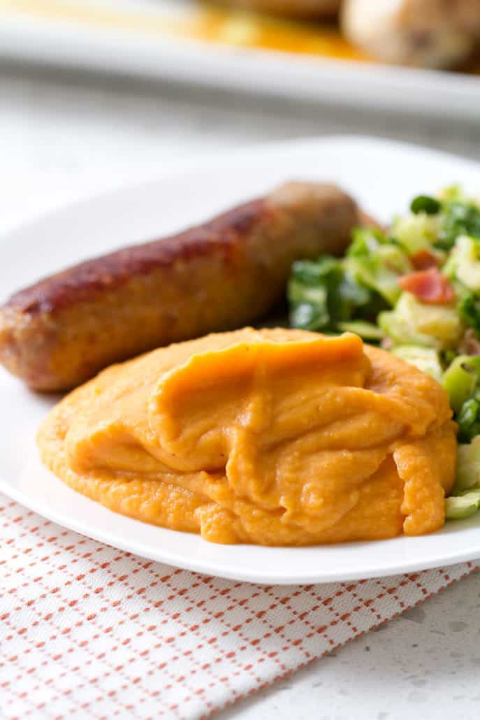 plate of mashed sweet potatoes, sausage and greens