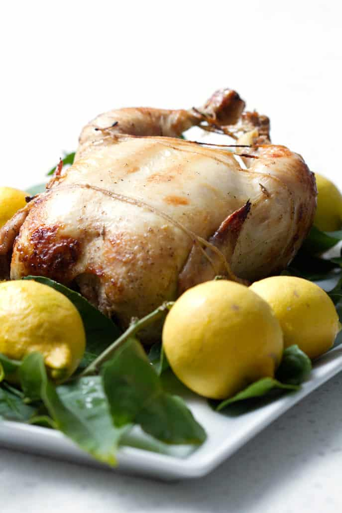 whole roasted chicken surrounded by lemons