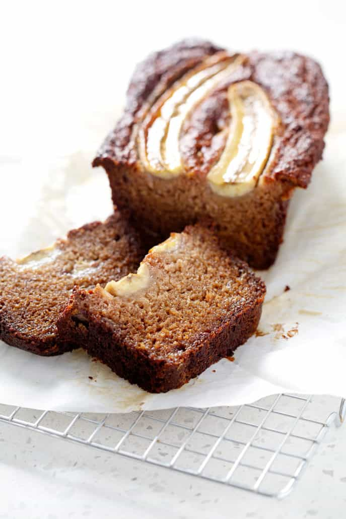 AIP banana bread loaf with slices on parchment and wire rack