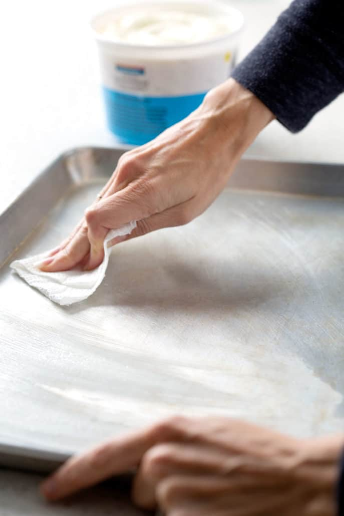 rubbing shortening onto baking sheet