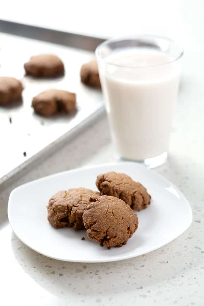 plate of cookies in front of glass of milk and baking sheet