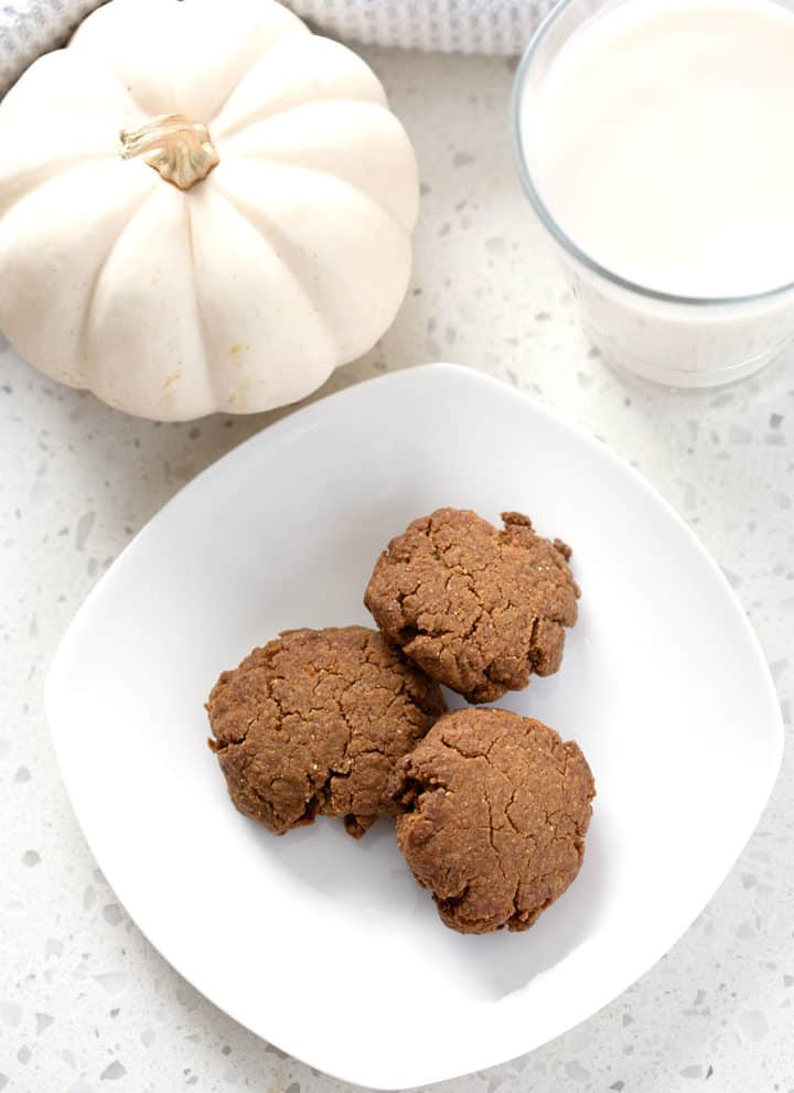 aip ginger cookies surrounded by pumpkin and glass of milk