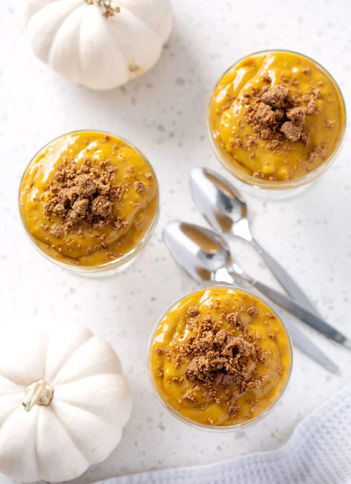 pumpkin pudding cups from above with pumpkins and spoons